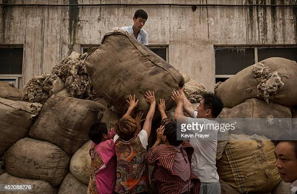 Chinese workers lift a large bag of sheep's wool that will later be processed and bleached at a factory on July 12 2014 near Zhangzhou China The...