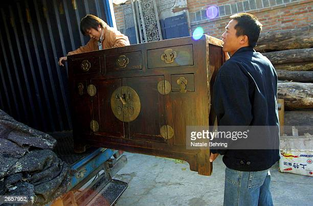 Chinese workers load antique furniture in to a truck to be sent to Spain at a factory October 27 2003 outside Beijing China Since their entry into...