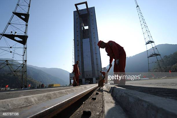 Chinese workers make final preparations to the launch pad at the Xichang Satellite Launch Centre in the southwestern province of Sichuan on December...