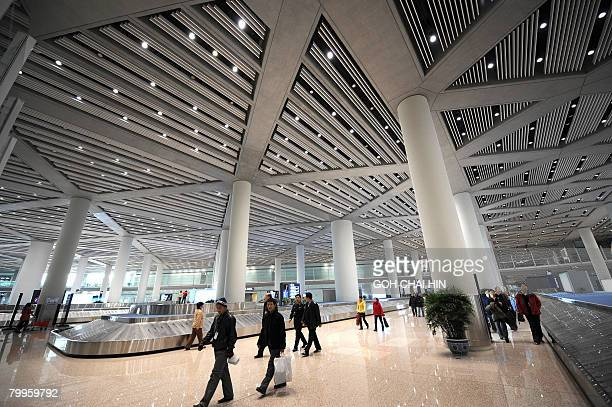 Chinese workers make their way pass the baggage conveyor belts at the new Terminal 3 of the Beijing Capital International Airport in Beijing on...