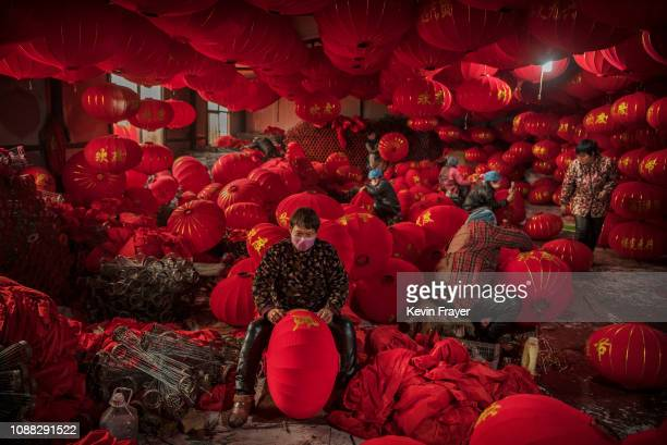 Chinese workers make traditional red lanterns at a local factory on January 24 2019 in the village of Tuntou in Hebei province China The village of...