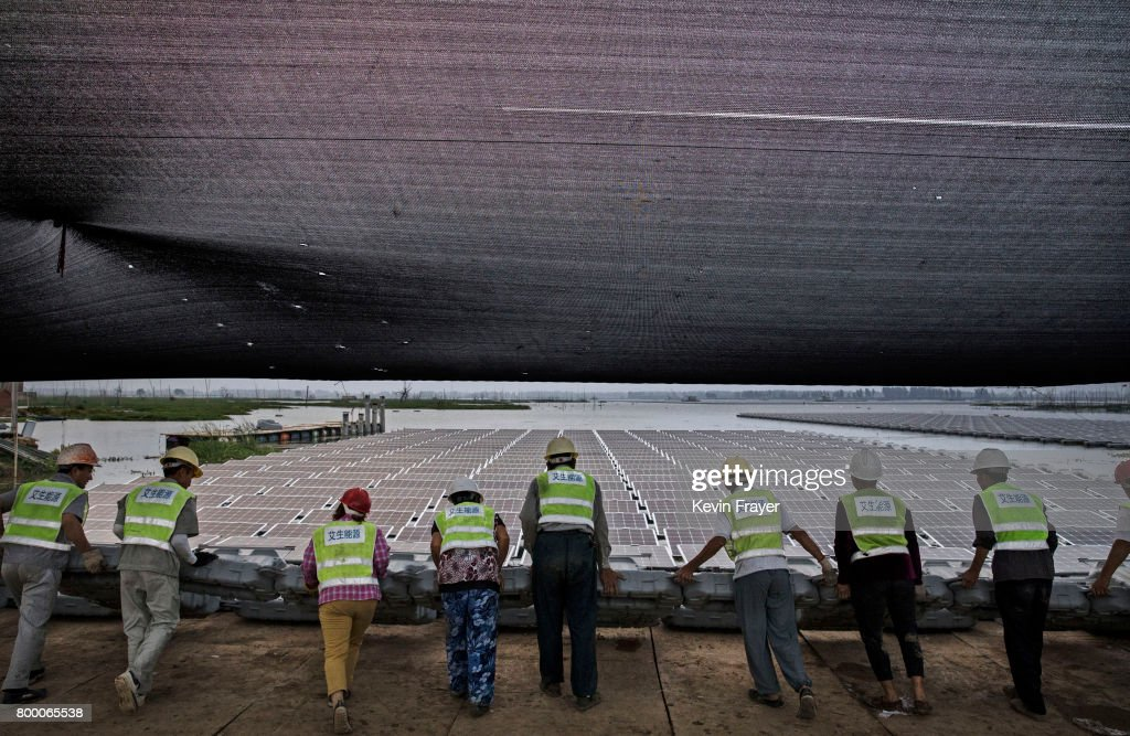 Chinese workers push a section of panels into the water that are part of a large floating solar farm project under construction by the Sungrow Power Supply Company on a lake caused by a collapsed and flooded coal mine on June 12, 2017 in Huainan, China. The floating solar field, billed as the largest in the world, is built on a part of the collapsed Panji No.1 coal mine that flooded over a decade ago due to over-mining, a common occurence in deep-well mining in China's coal heartland. When finished, the solar farm will be made up of more than 166,000 solar panels which convert sunlight to energy, and the site could potentially produce enough energy to power a city in Anhui province, regarded as one of the country's coal centers. Local officials say they are planning more projects like it, marking a significant shift in an area where long-term intensive coal mining has led to large areas of subsidence and environmental degradation. However, the energy transition has its challenges, primarily competitive pressure from the deeply-established coal industry that has at times led to delays in connecting solar projects to the state grid. China's government says it will spend over US $360 billion on clean energy projects by 2020 to help shift the country away from a dependence on fossil fuels, and earlier this year, Beijing canceled plans to build more than 100 coal-fired plants in a bid to ease overcapacity and limit carbon emissions. Already, China is the leading producer of solar energy, but it also remains the planet's top emitter of greenhouse gases and accounts for about half of the world's total coal consumption.