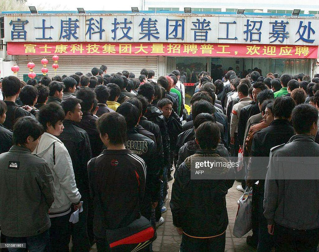 Chinese workers queue up for jobs at Foxconn's recruiting center in Shenzhen, southern China's Guangdong province on February 22, 2010, under a banner reading 'If you want a job with Foxconn, gather here.' A 19-year-old employee of Taiwanese technology giant Foxconn fell to his death on May 25, 2010, at the company's plant in southern China -- the 10th such death this year, raising questions about the conditions for millions of factory workers in China, especially at Foxconn, where labour activists say long hours, low pay and high pressure are the norm. CHINA