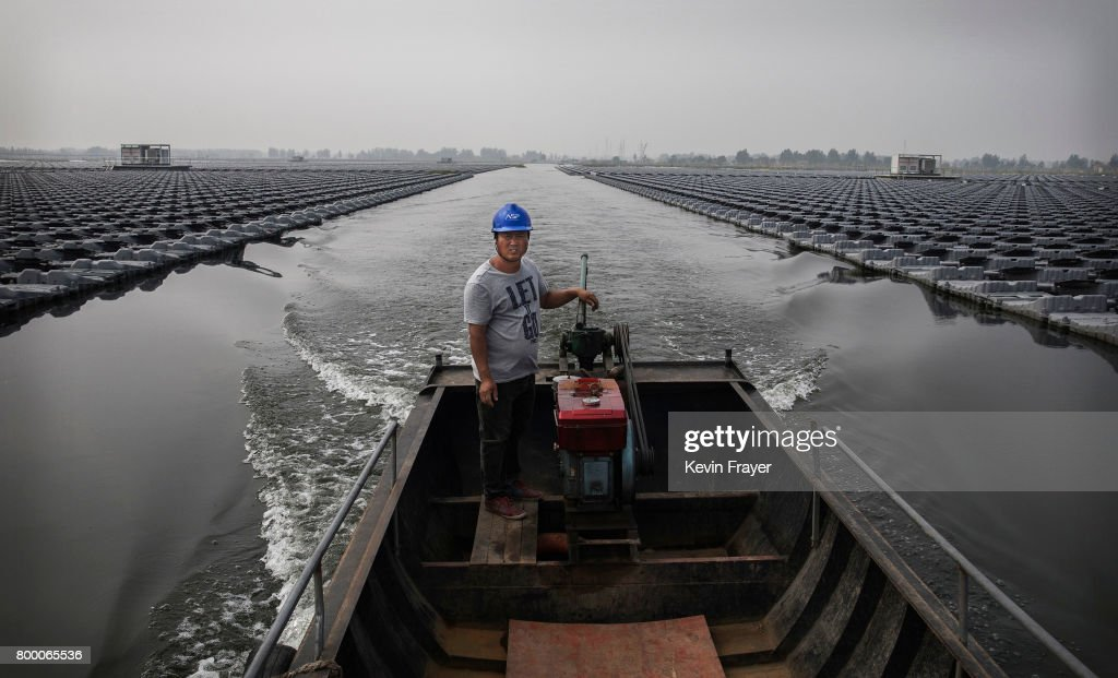 Chinese workers ride in a boat through a large floating solar farm project under construction by the Sungrow Power Supply Company on a lake caused by a collapsed and flooded coal mine on June 13, 2017 in Huainan, Anhui province, China. The floating solar field, billed as the largest in the world, is built on a part of the collapsed Panji No.1 coal mine that flooded over a decade ago due to over-mining, a common occurence in deep-well mining in China's coal heartland. When finished, the solar farm will be made up of more than 166,000 solar panels which convert sunlight to energy, and the site could potentially produce enough energy to power a city in Anhui province, regarded as one of the country's coal centers. Local officials say they are planning more projects like it, marking a significant shift in an area where long-term intensive coal mining has led to large areas of subsidence and environmental degradation. However, the energy transition has its challenges, primarily competitive pressure from the deeply-established coal industry that has at times led to delays in connecting solar projects to the state grid. China's government says it will spend over US $360 billion on clean energy projects by 2020 to help shift the country away from a dependence on fossil fuels, and earlier this year, Beijing canceled plans to build more than 100 coal-fired plants in a bid to ease overcapacity and limit carbon emissions. Already, China is the leading producer of solar energy, but it also remains the planet's top emitter of greenhouse gases and accounts for about half of the world's total coal consumption.