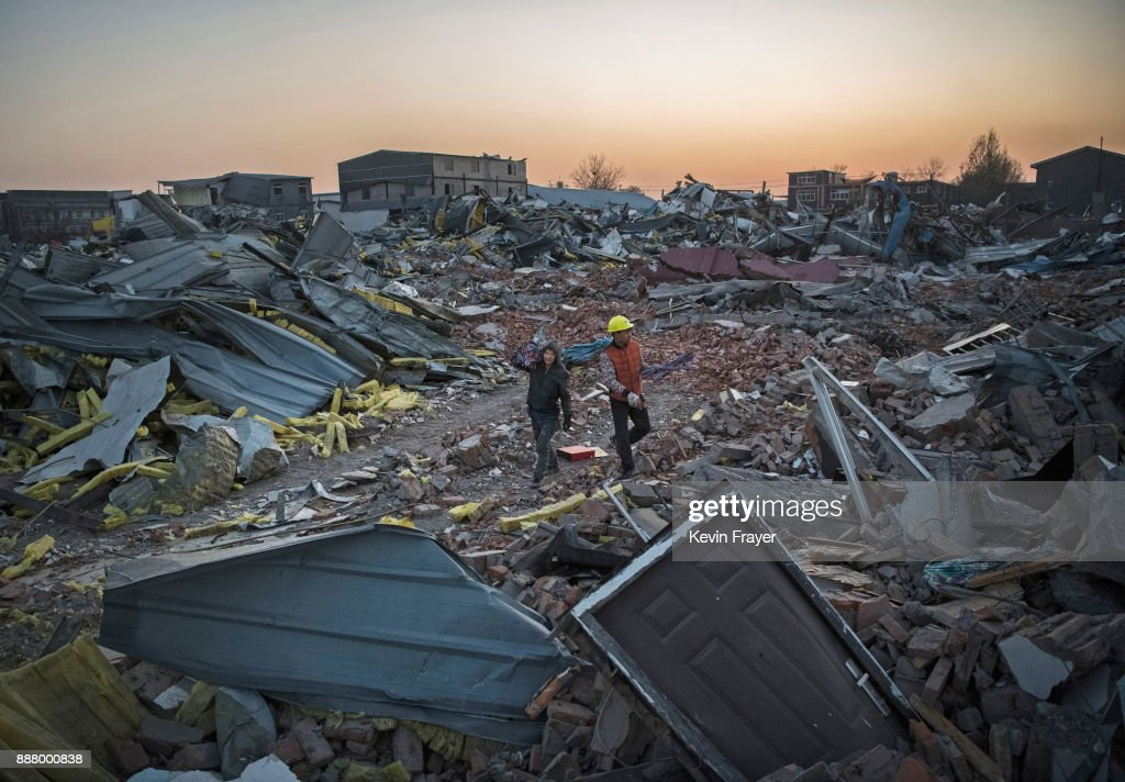 Chinese workers salvage items from buildings demolished by authorities in an area that used to have migrant housing and factories on December 6, 2017 in the Daxing District of Beijing, China.Thousands of migrant workers have been forcibly evicted in recent weeks in a sweeping government safety campaign following a deadly fire at a housing settlement. Many migrants, who came to Beijing from poor rural areas to find employment, say they were given little notice to leave and cannot afford to move somewhere else. The government's plan to demolish the buildings was actually announced in a 2015 strategy to reduce and cap the capital's population, but the mass evictions were accelerated after the fire and have stirred public backlash. The migrant population typically work in jobs such as construction, sanitation, and deliveries that have effectively built Beijing and keep it running. Some companies announced assistance and temporary housing for employees who have been affected, but many migrants say they have little choice but to move back to their hometowns.