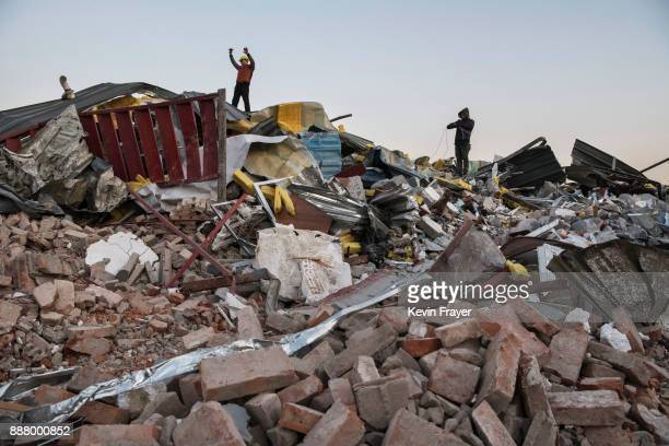 Chinese workers salvage items from buildings demolished by authorities in an area that used to have migrant housing and factories on December 6 2017...