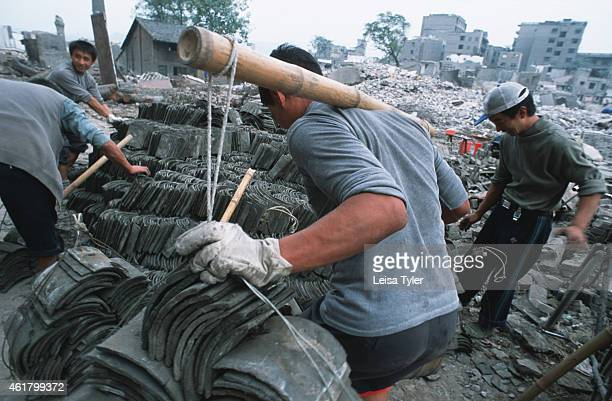 Chinese workers salvaging tiles from the remnants of Fengdu an ancient city on the shores of the Yangtze River that is being dismantled to make way...
