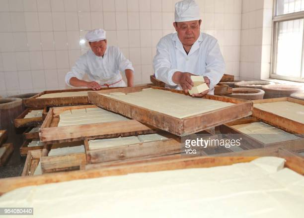 Chinese workers sort out tofu before making white fermented tofu on May 3 2018 in Qinhuangdao Hebei Province of China