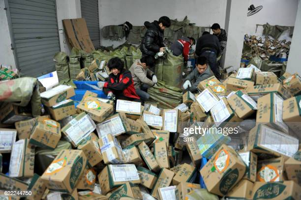Chinese workers sort through boxes of goods at a delivery company in Lin'an east China's Zhejiang province on November 11 2016 Chinese shoppers spent...
