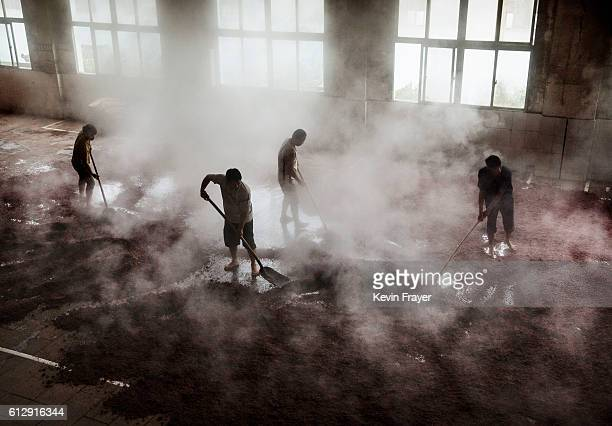 Chinese workers spread sorghum as it is prepared for the first fermentation to be used in locally made wine called baijiu at the Maopu Health Liquor...