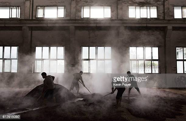 Chinese workers spread steamed sorghum on the ground as they prepare it for the first fermentation to be used in locally made wine called baijiu at...