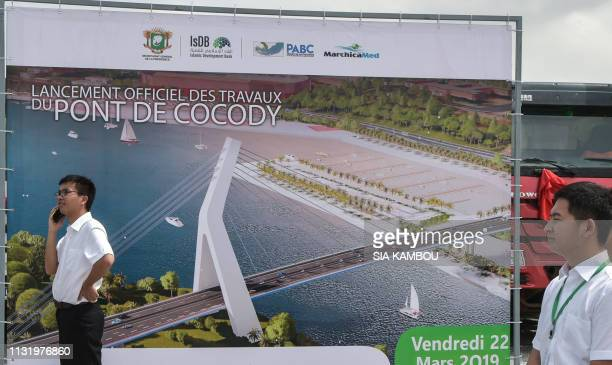 Chinese workers stand by a poster on March 22 2019 depicting a drawing of the 5th CocodyPlateau bridge in Abidjan during the official launch of the...