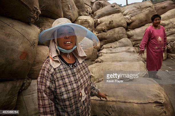 Chinese workers stand next to bags of sheep's wool imported from Australia that will later be cleaned and bleached at a factory on July 12 2014 near...