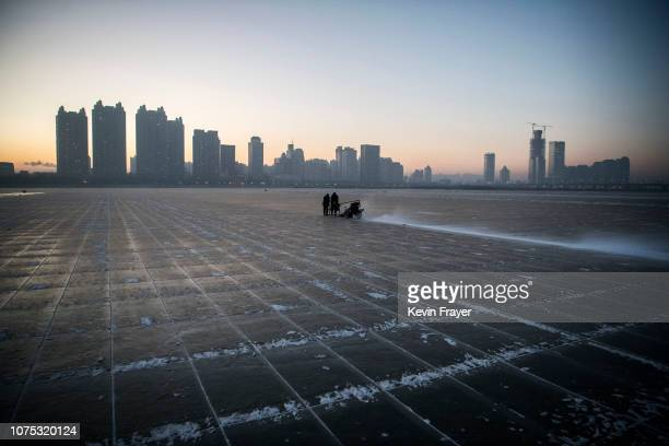 Chinese workers use use a machine to cut into large blocks of ice that will be used in the making of ice sculptures from the frozen Songhua River in...