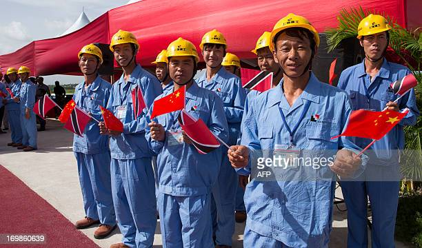 Chinese workers wait for the arrival of Chinese President Xi Jinping at the site of the Couva Children's Hospital, in which construction they...
