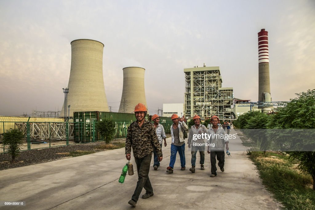 Chinese workers walk along a path at the Sahiwal coal power plant owned by China`s stateowned Huaneng Shandong Rui Group in Sahiwal Punjab Pakistan...