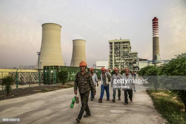 Chinese workers walk along a path at the Sahiwal coal power plant owned by China's stateowned Huaneng Shandong Rui Group in Sahiwal Punjab Pakistan...