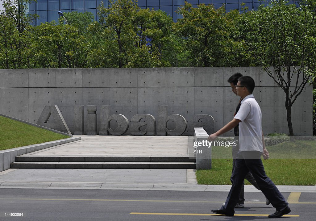 Chinese workers walk by the Alibaba head : News Photo