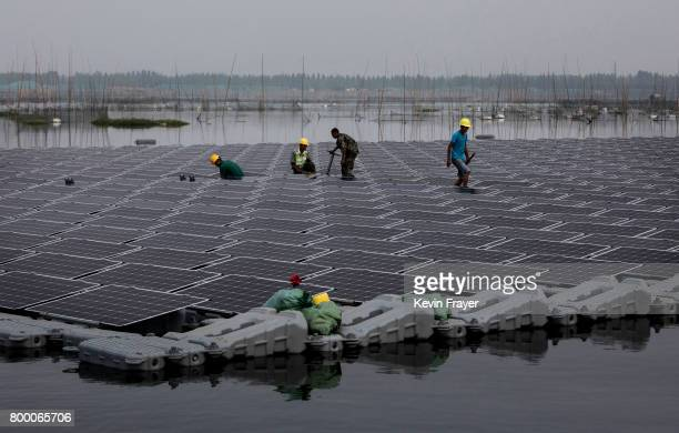 Chinese workers walk on a section of a large floating solar farm project under construction by the Sungrow Power Supply Company on a lake caused by a...