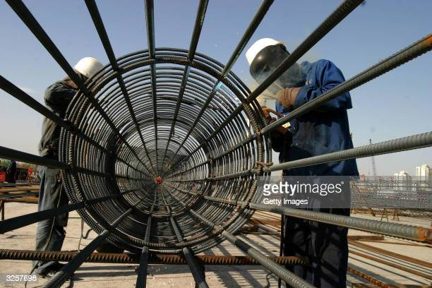 Chinese workers weld a steel pillar on the site of the National Olympic Stadium April 8 2004 in Beijing The National Stadium is being built by a...