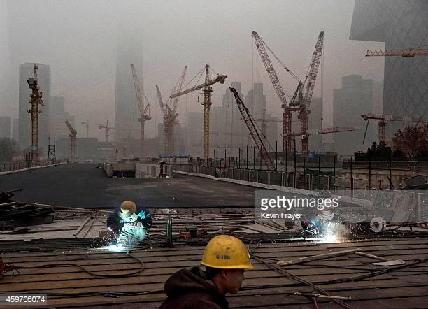 Chinese workers weld at a construction site in heavy pollution on November 29 2014 in Beijing China United States President Barack Obama and China's...