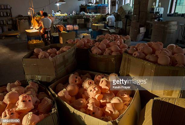 Chinese workers work on a line as doll heads are seen in boxes at a toy factory on September 17 2015 in Xietang Zhejiang Province China Many of the...