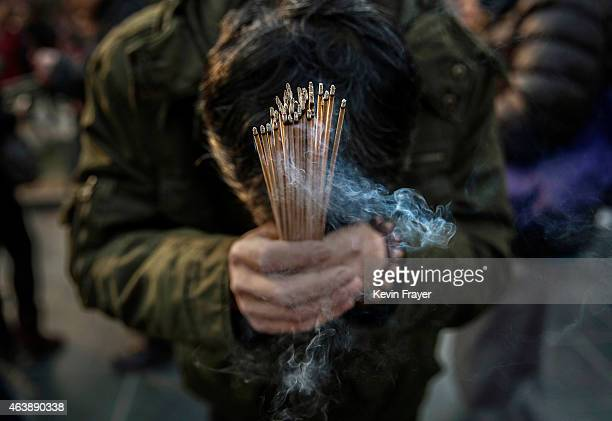 Chinese worshipper holds incense while praying with others at the Yonghegong Lama Temple during celebrations for the Lunar New Year February 19 2015...