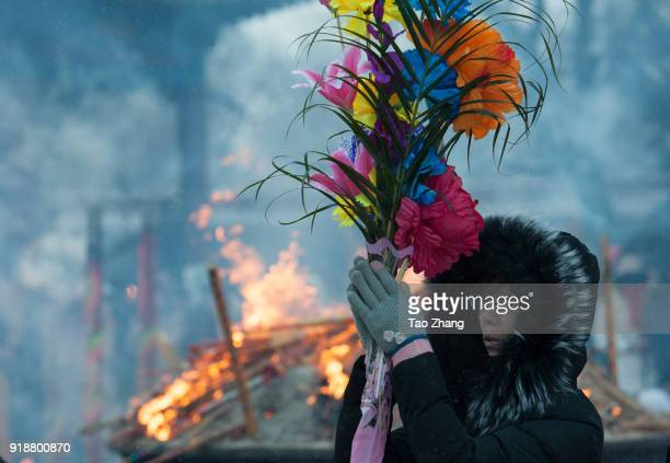 Chinese worshipper takes flower to pray happiness and good health at the Dacheng Temple on February 16 2018 in QiqiharChina Chinese New Year is being...