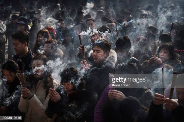 Chinese worshippers hold incense as they pray for good fortune on the first day of the Lunar New Year at Yonghegong or Lama Temple on February 5 2019...