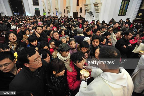 Chinese worshippers receive the Eucharist from a priest as they attend Christmas Eve mass at a Catholic church in Wuhan central China's Hubei...