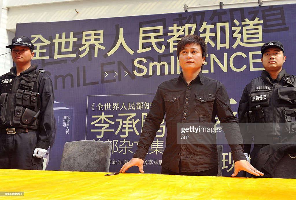 Chinese writer Li Chengpeng, looked upon by many as a a highly influential Chinese blogger and social commentator, is protected by bodyguards as he attends a promotional event of his new book 'SmILENCE' on January 26, 2013 in Kunming, southwest China's Yunnan province. Li was attacked by Maoists earlier at his book signings in Beijing and Shenzhen, forcing him to cancel two others in Guangzhou and Changsha. The Maoists take offence to Li's caustic essays and comments about the Communist Party's governance. Li has previously been punched in the head at a previous signing. CHINA