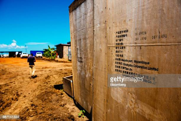 Chinese writing reading 'Sinohydro Corporation Limited' and Luoyang Xinsilu Electric Co' sits on the side of wooden boards at the construction site...