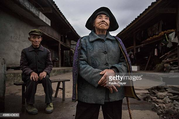 Chinese Yi minority villagers Qiu Kaibin left and Mao Guixiang stand outside their farmhouse in the hills below the 7556 m Mount Gongga known in...