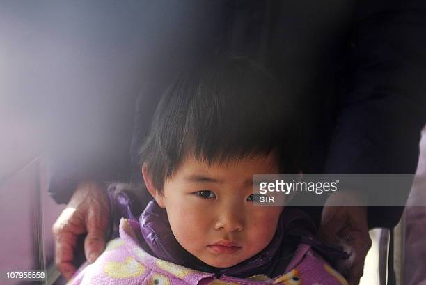 A Chinese young boy waits to receive treatment for lead poisoning at a hospital in Huaining east China's Anhui province on January 8 after...