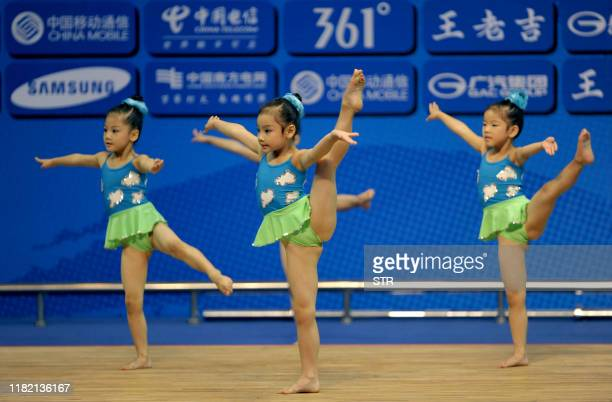 Chinese young girls perform during a break in the men's -62kg weightlifting event at the 16th Asian Games in Guangzhou on November 14, 2010. Athletes...