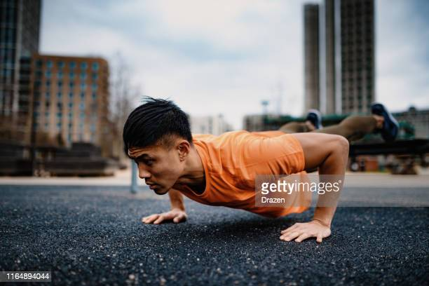 chinese young man exercising on cloudy day, doing push ups - practising stock pictures, royalty-free photos & images