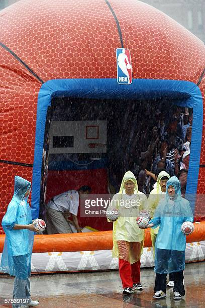Chinese youth play basketball in front of a basketballshaped decoration in the NBA Jam Van on May 5 2006 in Nanjing of Jiangsu Province China NBA Jam...