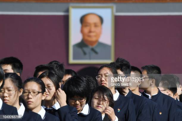 Chinese youths wait near a portrait of late communist leader Mao Zedong before a ceremony in Beijing's Tiananmen Square on the eve of National Day on...