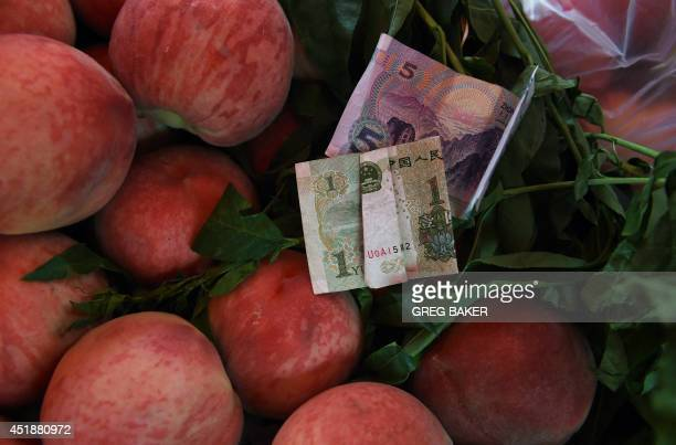 Chinese Yuan notes are seen on peaches at an outdoor market in Beijing on July 9 2014 China's annual inflation slowed to 23 percent in June from a...