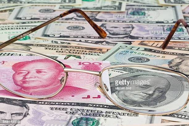 Chinese Yuan Renminbi with portrait of Mao Zedong and Dollar banknotes with portrait of George Washington seen through glasses