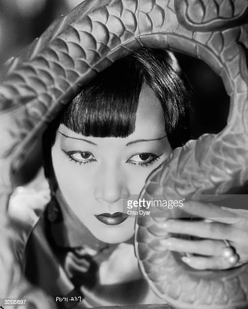 ChineseAmerican film star Anna May Wong poses with her head framed by an oriental carving