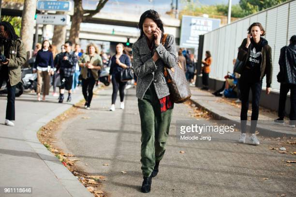 Chinese/French model Mae Lapres talks on the phone and wears a vintage Yves Saint Laurent gray tweed jacket Louis Vuitton leather logo purse loose...