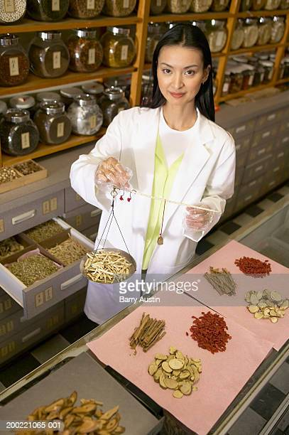 Chinese-herbalist behind counter with herbs, smiling, portrait