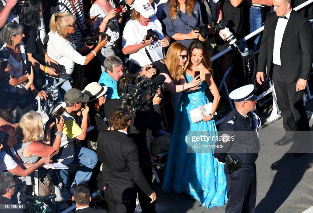 Chinese-Malaysian actress Michelle Yeoh poses for selfies as she arrives on May 17, 2017 for the screening of the film 'Ismael's Ghosts' (Les Fantomes d'Ismael) during the opening ceremony of the 70th edition of the Cannes Film Festival in Cannes, southern France. /