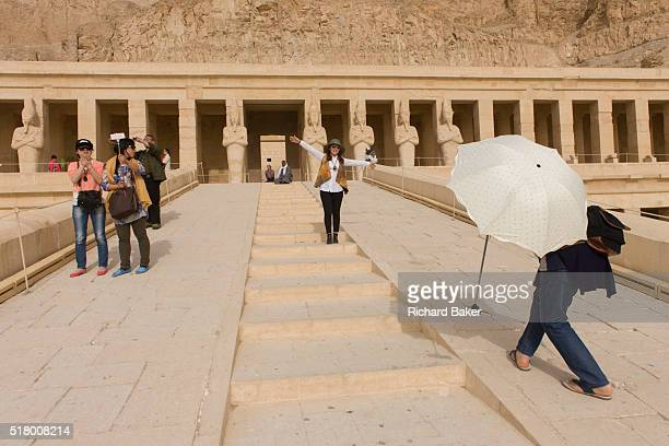A Chinesespeaking tourist group enjoy the experience of visiting the ancient Egyptian Temple of Hatshepsut near the Valley of the Kings Luxor Nile...