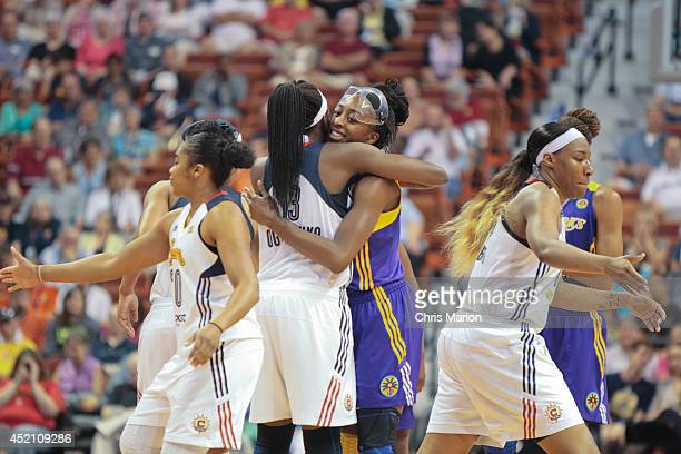 Chiney Ogwumike of the Connecticut Sun and Nneka Ogwumike of the Los Angeles Sparks hug prior to a game at the Mohegan Sun Arena on July 13 2014 in...