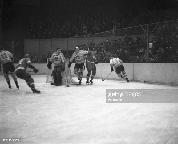 Ching Johnson, hand on the goal post as he tried to block out Pettinger of the Red Wings carrying the puck. The New York Americans handed the Stanley...