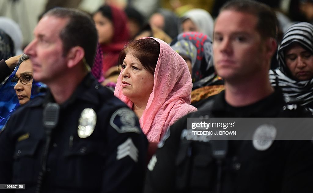 Chino police officers and San Bernardino County Sheriff's Department officers join Muslims from the Ahmadiyya Muslim Community for a vigil at the Baitul Hameed Mosque in Chino, California on December 3, 2015, to commemorate lives lost a day after the tragedy in San Bernardino. A young couple who killed 14 people in a shooting in California had amassed a huge arsenal and carefully planned their attack, authorities said, refusing to rule out terrorism.