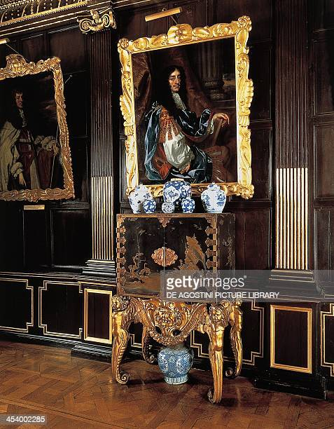 Chinoiserie, lacquered cabinet, 1630-1650, Dutch support in gilt and carved wood, with a portrait of Charles II of England on the wall by the School...