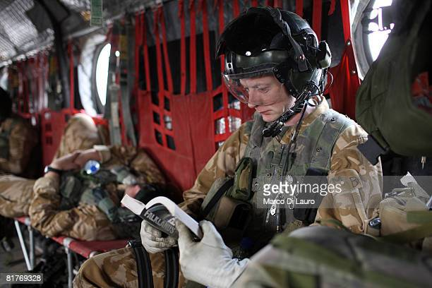 Chinook 27th Squadron Royal Air Force air crew member part of the Joint Helicopter Force reads a book as he travels on a Chinook helicopter with...
